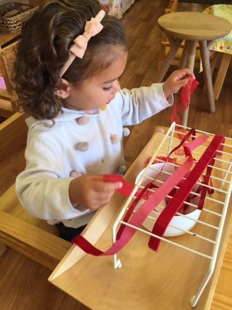 Rockingham Montessori infant toddler tying ribbons