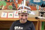 Rockingham Montessori student wearing a paper hat during Upper Primary's art showcase