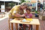 Rockingham Montessori teacher teaching a student how to polish a mug