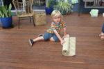 Rockingham Montessori male student rolling a mat on the floor