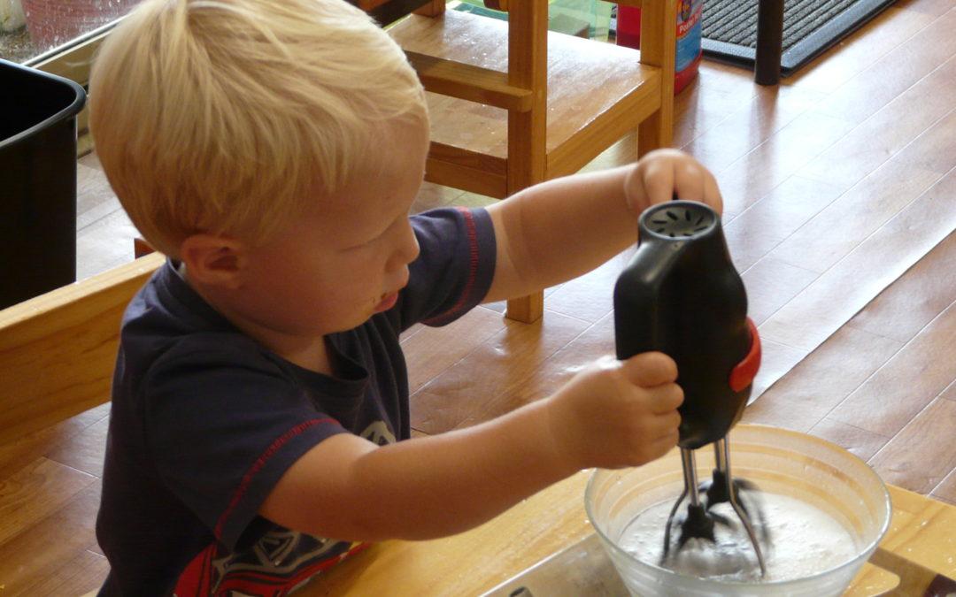 Rockingham Montessori infant toddler holding a manual mixer