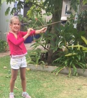 Rockingham Montessori School female student shooting a bow and arrow