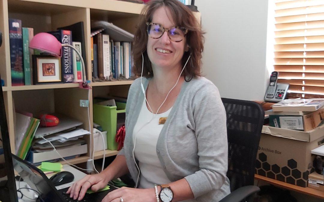 Rockingham Montessori School female teacher working with a laptop in her workspace